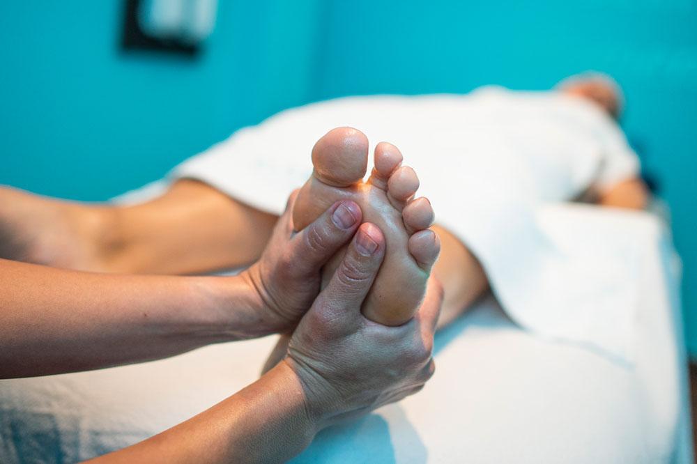 Fußreflexzonenmassage mit beiden Daumen an der linken Fußsohle