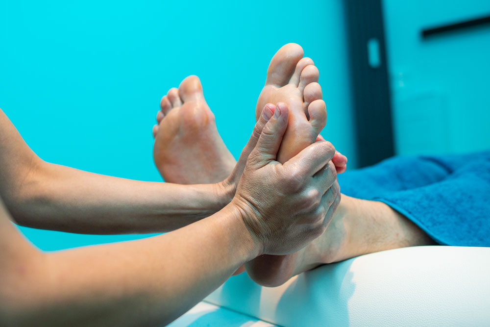 Fußreflexzonenmassage mit beiden Händen an der linken Fußsohle